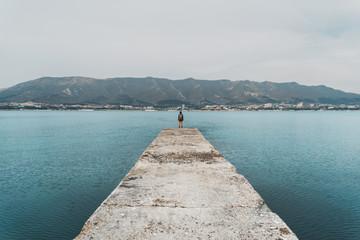 Hiker woman standing on pier