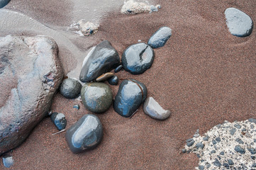 Pebbles on a red sandy beach