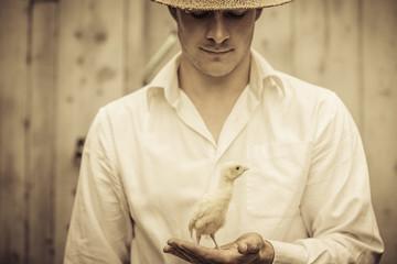 Farmer Holding a Baby Turkey