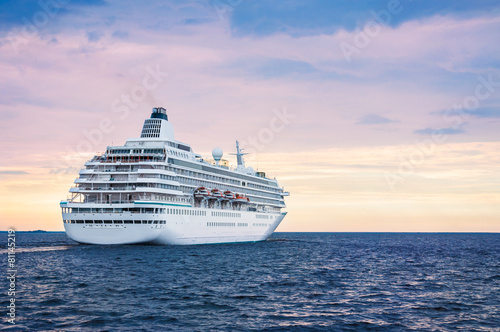 Leinwanddruck Bild Big cruise ship in the sea at sunset