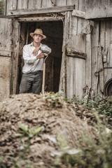 Farmer Shoveling the Horse Manure
