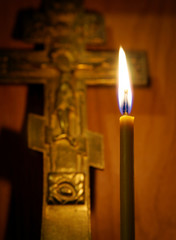 Burning candle and ancient Christian cross. Focus on a candle