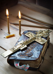 Christian still life with ancient book and burning candles