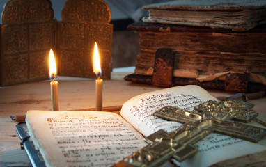 Two candles and an old metal cross on the open Psalter