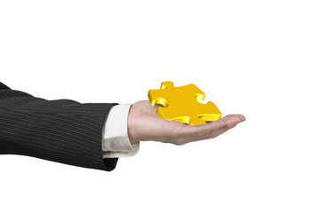Hand showing gold jigsaw puzzle piece isolated on white