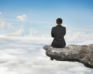 Rear view businessman sitting on cliff with natural sky cloudsca