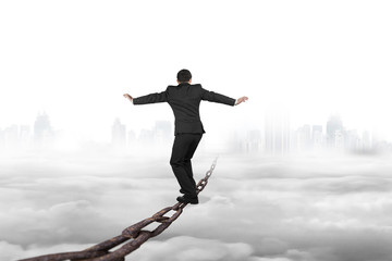 Businessman balancing on old iron chain with cloudy sky cityscap