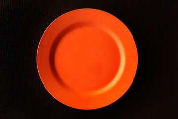 Empty Plate - Orange round empty plate on wooden background.