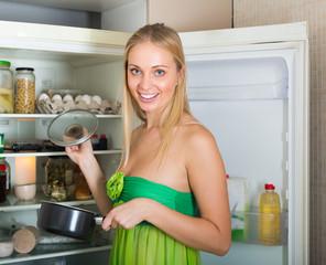 Blonde woman near refrigerator