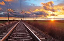 "Постер, картина, фотообои ""Orange sunset in low clouds over railroad"""