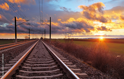 Orange sunset in low clouds over railroad Poster
