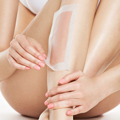woman depilating legs by waxing