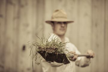 Farmer with a Shovel Full of Grass