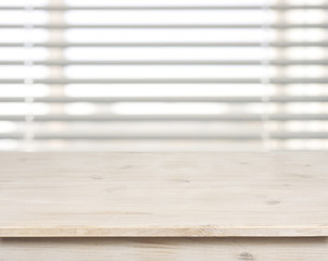 Wooden table on defocuced window with venetian blinds background