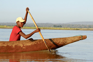 Young Malagasy african boy rowing traditional canoe on river