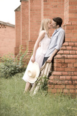 Happy couple kissing outdoors against building in green grass