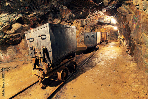 Leinwanddruck Bild Mining cart in silver, gold, copper mine