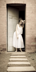 Attractive young woman leaning in doorway