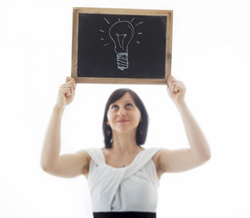 businesswoman shows doodle of a light bulb on blackboard