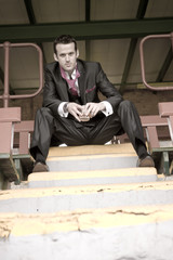 Handsome young man in suit sitting on yellow strip staircase