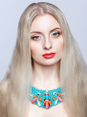 Beautiful blonde woman in bijouterie  on grey background