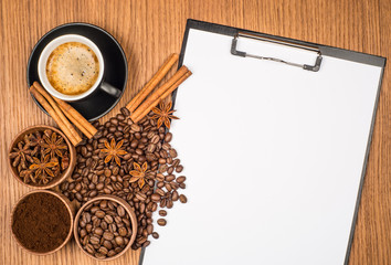 A cup of coffee, star anise, cinnamon and a clipboard with blank