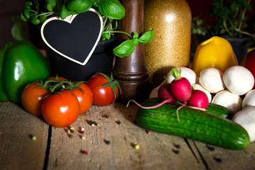 Holztisch mit viel frischem Gemüse und Kräuter, Herz mit Textf