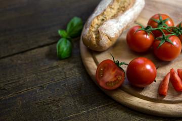 Tomaten mit rustikalem Brot und Basilikum auf Holztisch