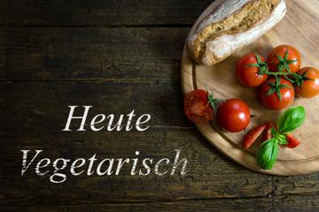 Tomaten mit Brotlaib auf Holztisch mit Text Heute Vegetarisch