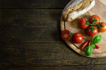 Frische Tomaten mit Basilikum und rustikalem Brot auf Holztisch
