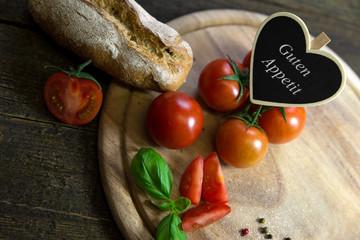 Tomaten mit Brotlaib auf Holztisch, Herz mit Text Guten Appetit