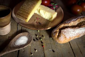 Rustikales Brot mit Käse, Salz und Tomaten auf altem Holztisch