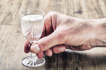 Alcoholism. Hand alcoholic and drink the distillate