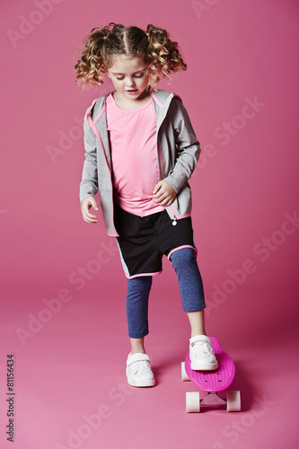 Girl skateboarding in studio - 81156434