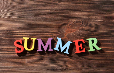 Word summer on wooden background