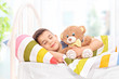 Lovely boy sleeping with a teddy bear in a bed