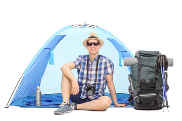 Male camper sitting in front of a blue tent