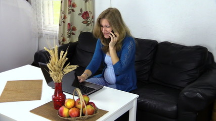 pregnant business woman talk phone and work with laptop at home
