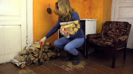 pregnant woman in sweater and jeans carry axe and firewood