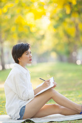 young woman sitting on green grass park with pencil and note boo
