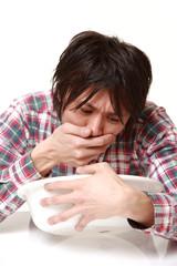 嘔吐する男性