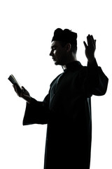 man priest silhouette reading bible
