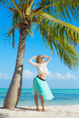 Young happy woman standing on beach under palm tree