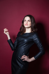 Portrait of young beautiful woman in leather dress on red