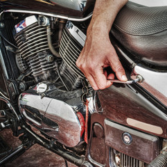 man repairing a classic motorcycle in hdr