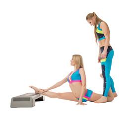 Pretty female gymnasts warming up in studio