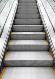 Shining metal escalator moving up, vertical photo