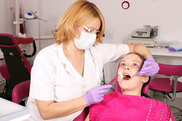 female dentist and girl patient in dentist office