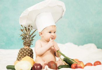 little baby in chef hat tasting green onion