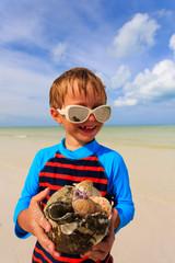 little boy holding seashells on summer tropical beach